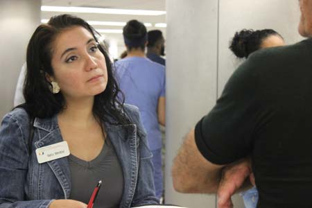 Nancy Mendoza, a Miami Law L.L.M. student from Venezuela, interviews a Cuban resident in Miami as he waits for family to arrive from Havana at the Miami International Airport.
