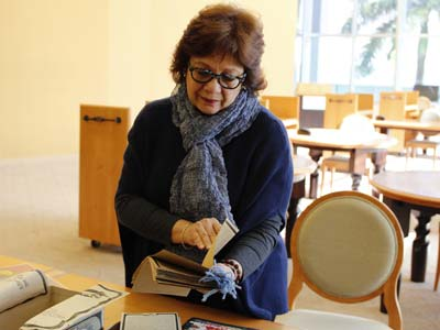 Lilian Manzor, associate professor and chair of the Department of Modern Languages and Literatures in the College of Arts and Sciences, leafs through historical theater materials, also digitally archived, at the UM Cuban Heritage Collection.