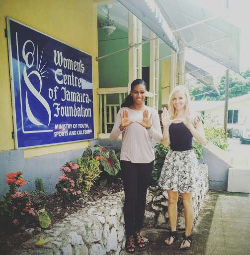 Soroya McFarlane, left, and Kerli Kirch throw up the U in front of the Women's Centre of Jamaica Foundation in downtown Kingston.