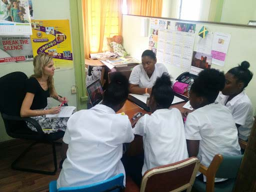Kerli Kirch sits with Jamaican teenage girls at the Women's Centre of Jamaica Foundation in Kingston.
