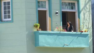 A woman peers from a balcony in downtown Havana, Cuba.